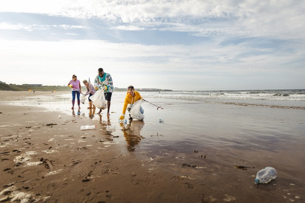 Collecting rubbish off a beach. Plastic containers, bottles in their bag. They are using a mechanical grabber. Three women and a man working together