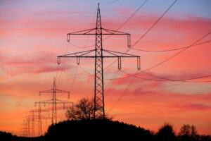 Electricity pylons silhouetted against a dramatic sunset
